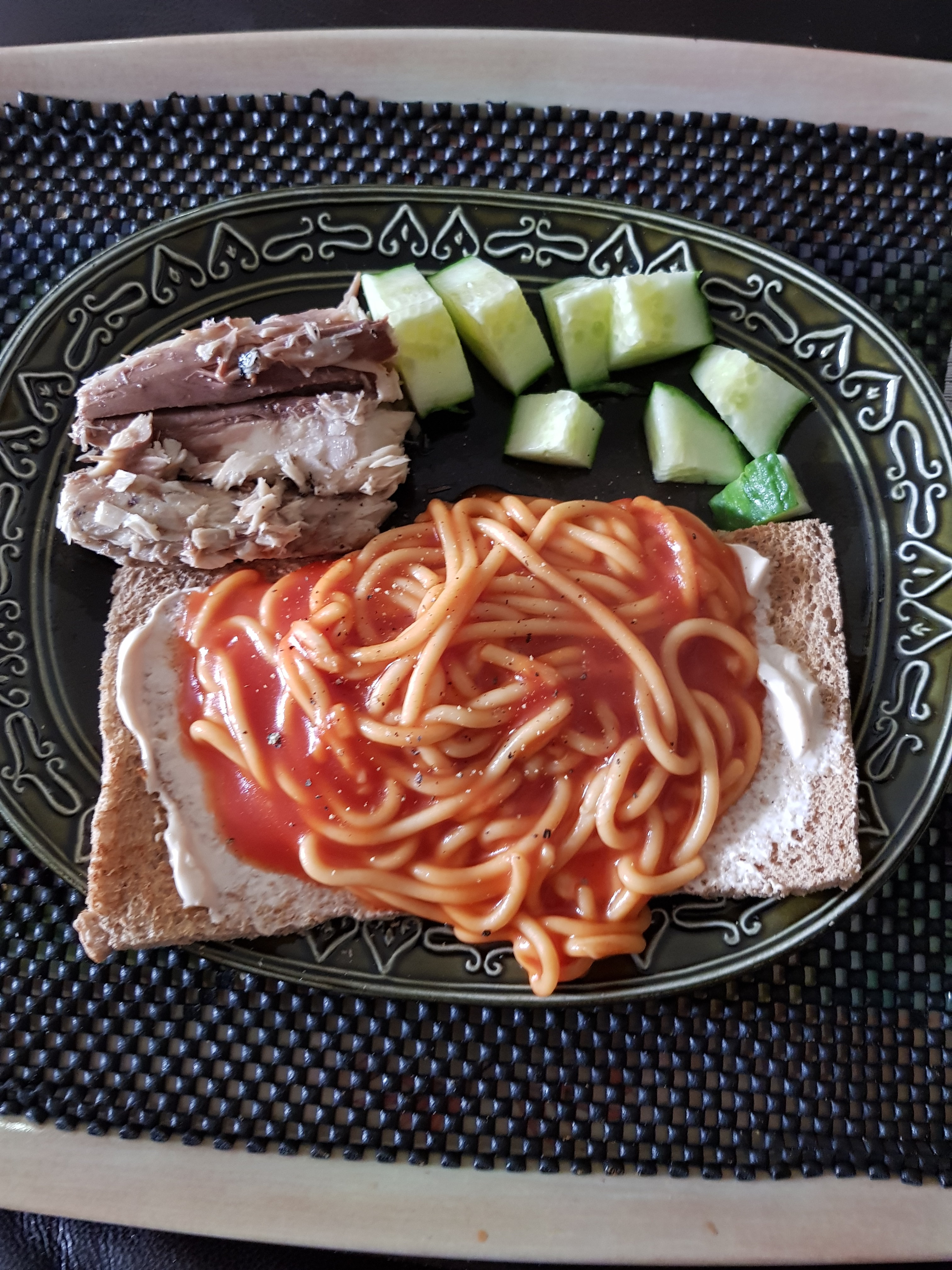 Lunch of spaghetti on wholemeal toast, mackerel and cucumber